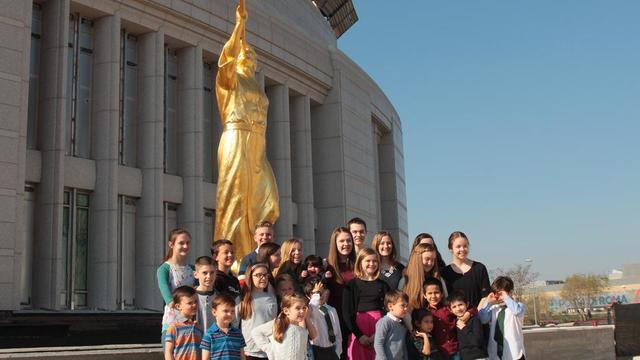 Children in Italy pose with the angel Moroni statue