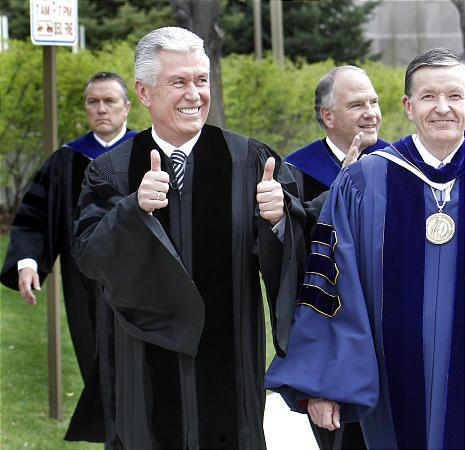 President Dieter F. Uchtdorf walks with BYU President Cecil O. Samuelson and gives a thumbs-up to graduates at the 2009 spring commencement at the Marriott Center.
