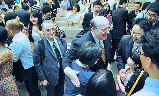 Image titleElder Cook greeting members in Asia. Image from Facebook.