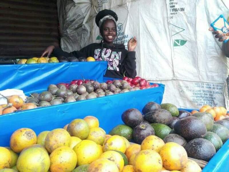 Susan's daughter, Serena, at a fruit stand.